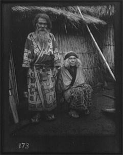 Arnold Genthe. Ainu man and seated woman at the entrance of a hut (1908)