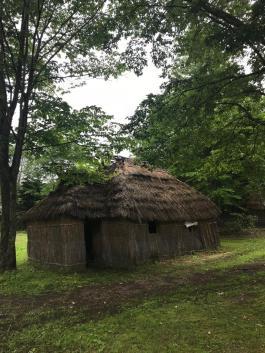 """Vilarejo Ainu. 'Uma casa Ainu tradicional é chamada de """"Chise"""", e é feita de folhas de bambu, palha, ou casca de árvores. As casas são alinhadas de leste a oeste em um Kotan.'"""